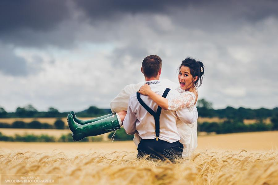 Groom carrying bride in a wheat field